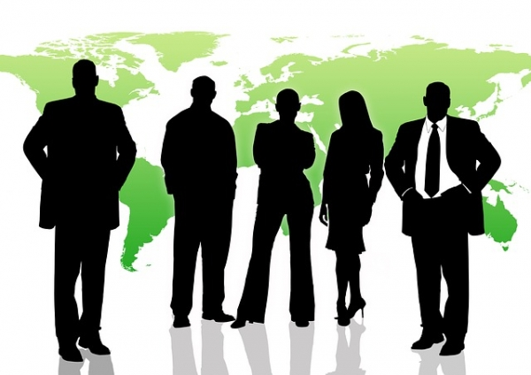 business men and women in front of a map of the world